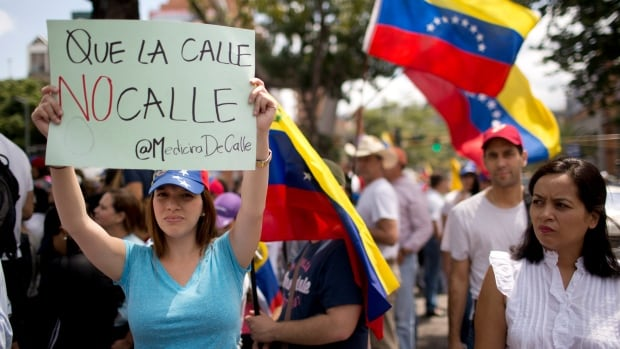"A woman holds up a banner with a play on the word ""calle"" that reads in Spanish; ""Don't let the streets get quiet,"" during a rally with human rights activists, in Caracas, Venezuela, Friday."