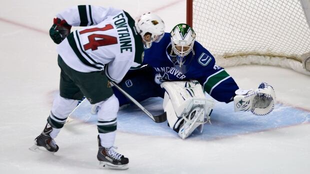 Minnesota Wild's Justin Fontaine, left, puts the puck under the leg of Vancouver Canucks' goalie Eddie Lack, of Sweden, to score the winning and only goal of the shootout Friday.