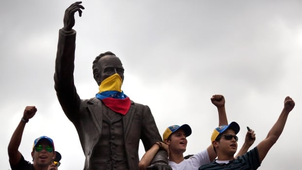 Demonstrators chant anti-government slogans next to a statue of Cuban writer and hero Jose Marti masked with a Venezuelan flag in Caracas, Venezuela, Sunday, March 2, 2014.
