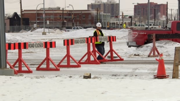 A worker puts up road blocks as construction started on the downtown arena Monday morning.