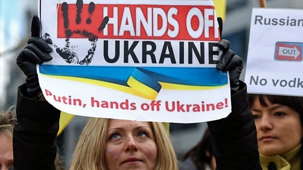 A handful of protesters gathered outside an emergency meeting of European Union foreign ministers in Brussels on Monday to protest against Russian troops in Ukraine.