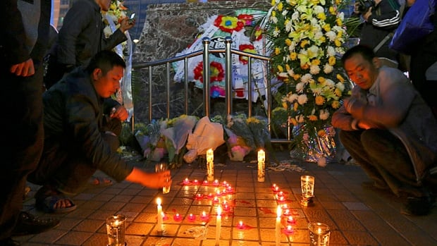 People light candles in front of wreaths outside Kunming railway station following Saturday's knife attack, one of the worst acts of mass murder in recent Chinese history.