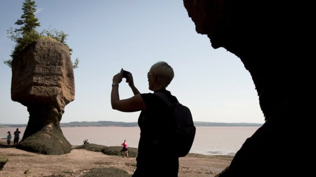 A tourist stops to take a photo of the Hopewell Rocks on the Bay of Fundy.