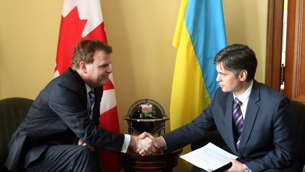 Canadian Foreign Affairs Minister John Baird (left) shakes hands with Vadym Prystaiko, Ukrainian ambassador to Canada, as they meet on Parliament Hill in March 2014.