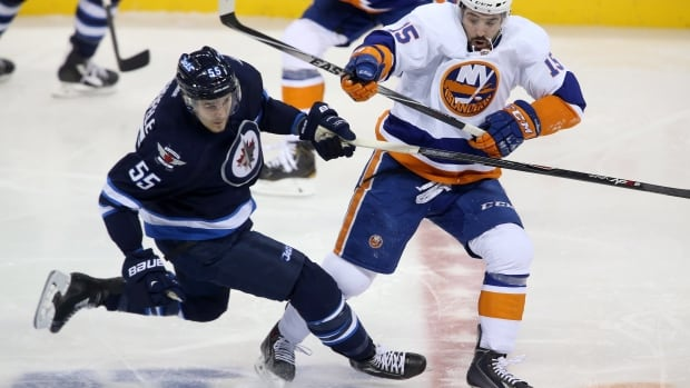 The Winnipeg Jets' Mark Scheifele, left, is checked by the New York Islanders' Cal Clutterbuck during first period Tuesday night at the MTS Centre.