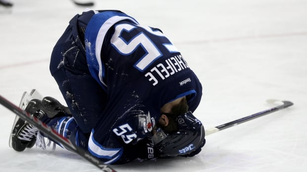 The Winnipeg Jets' Mark Scheifele is hurt on the ice against the New York Islanders during the second period March 4 at the MTS Centre.