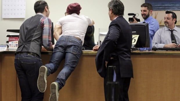 David Wilk leaps across the counter to hug Cook County Clerk's office employee Louisa Nicotera after obtaining a marriage licence with partner Charlie Gurion in February. Same-sex couples across Illinois can now get a marriage licence even though gay marriage isn't set to become law until June.