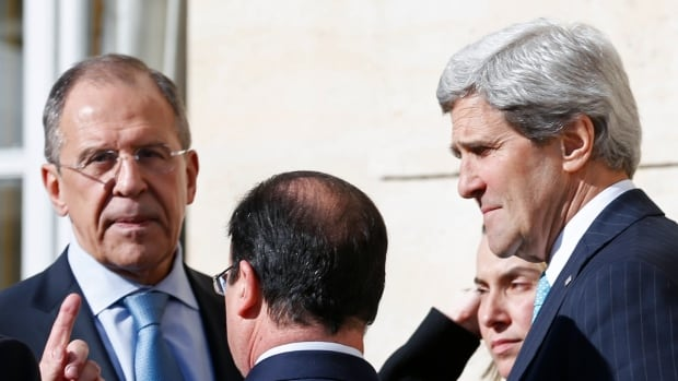 Russia's Foreign Minister Sergei Lavrov, left, and U.S. Secretary of State John Kerry, far right, speak Wednesday before their first face-to-face discussion since Russian troops effectively occupied Ukraine's Crimean Peninsula.