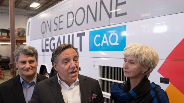 Coalition Avenir Québec François Legault, flanked by his wife Isabelle Brais, right, and candidate Gerard Deltell, left, unveils his campaign bus in Quebec City.