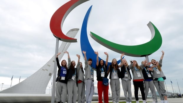 Spectators pose for a photograph on Thursday next to a sculpture of the official symbol of the 11th Paralympic Games, which begin Friday in Sochi, Russia.