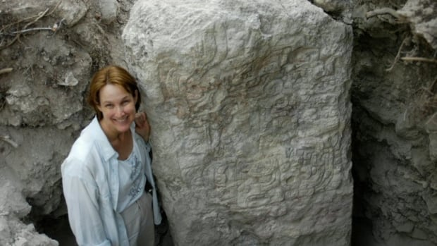 University of Calgary archaeologist Kathryn Reese-Taylor stands beside a stela, one of the large carved hieroglyphic pillars on which the Mayans commemorated significant events.