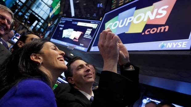 Coupons.com President & CEO Steven Boal and his wife Michele Boal photograph the company's logo before the stock opens  for trading in New York on Friday.