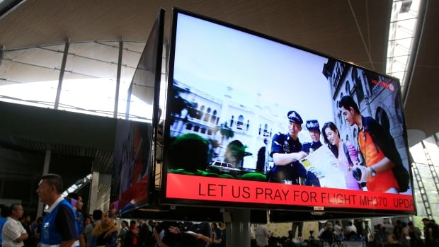 "An information screen shows ""Let us pray for Flight MH370"" at Kuala Lumpur International Airport in Sepang, outside Kuala Lumpur, Malaysia, on Saturday. The Malaysia Airlines Boeing 777-200 carrying 239 people lost contact over the South China Sea early Saturday morning on a flight from Kuala Lumpur to Beijing, and international aviation authorities still hadn't located the jetliner several hours later."
