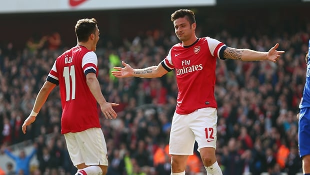 Olivier Giroud of Arsenal celebrates with teammate Mesut Ozil after scoring against Everton at Emirates Stadium on March 8, 2014 in London, England.