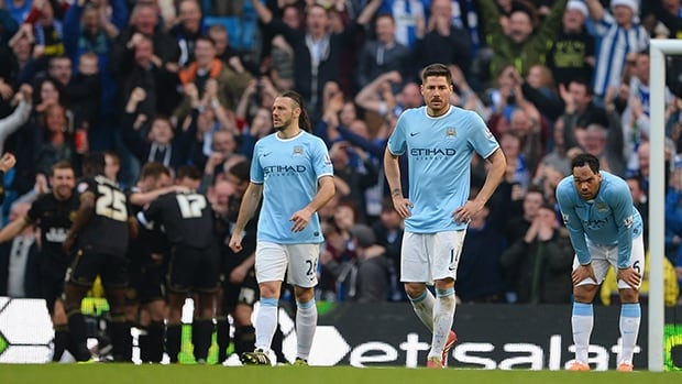 Manchester City players look dejected as Wigan celebrate a goal at the Etihad Stadium on March 9, 2014 in Manchester, England.