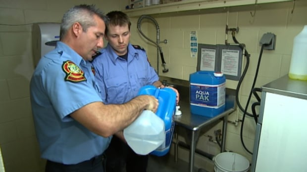 Two firefighters fill up jugs of potable water to be delivered to Winnipeg homes. More than 800 homes are waiting for city crews to thaw their frozen pipes.