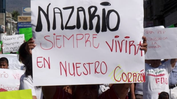 """A man holds a sign that reads in Spanish """"Nazario will always live in our hearts,"""" referring to La Familia drug cartel leader Nazario Moreno Gonzalez during a demonstration after the government announced he was killed in Apatzingan, Mexico."""