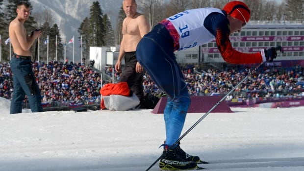 Shirtless onlookers watch as Russia's Vladislav Lekomtcev races in the men's cross-country 20-kilometre race on Monday. Temperatures in Sochi are hovering at about 15 C.