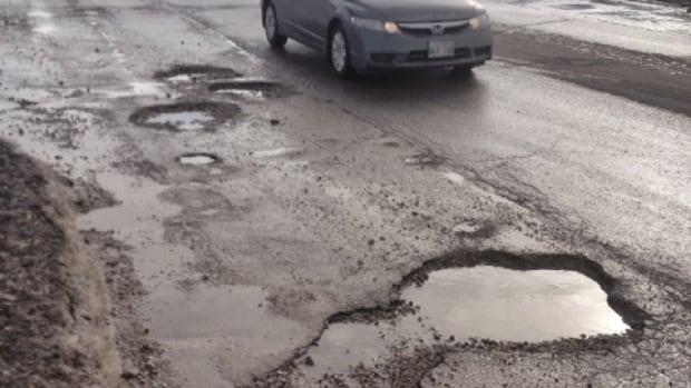 Massive potholes dot Empress Street at St. Matthews Avenue in Winnipeg.