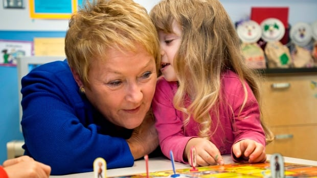 A young girl whispers her name in the ear of Quebec Premier Pauline Marois at a daycare, Monday, November 12, 2012 in Montreal. Marois announced new places in daycare.