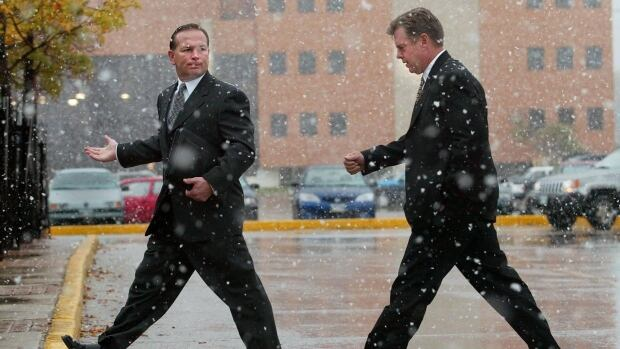 Businessmen walk in the snow. The tough winter weather that North America has experienced these past 3 months is holding back the economy, the OECD says.