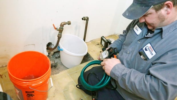 A plumber prepares a pump to shoot water into an incoming city water line in Minneapolis after the pipes froze. Plumbers have been inundated with calls across the Canadian Prairies and in a handful of states.