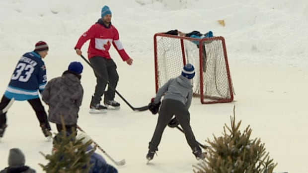 Skaters play a pick-up shinny game on the hockey rink at the Forks on Sunday.