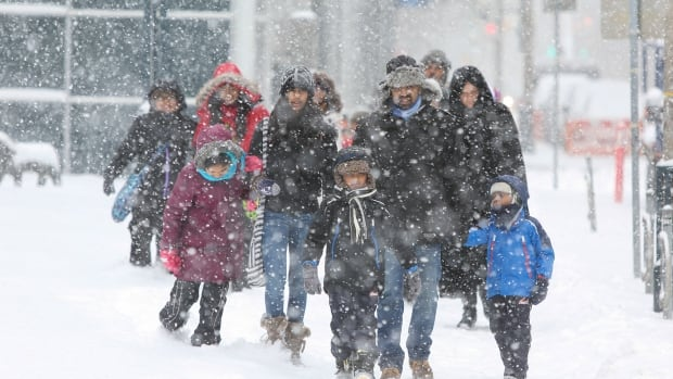 Family members bundled up against the snow make their way along Wellington Street in downtown Toronto on Wednesday as 15 centimetres of snow fell across southern Ontario, snarling the evening commute and leading to several multi-vehicle pileups along highways.