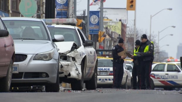 Officers attend the scene after a high-speed chase in Toronto on March 10. John Brown evaded capture when the pursuing police cruiser struck another vehicle.
