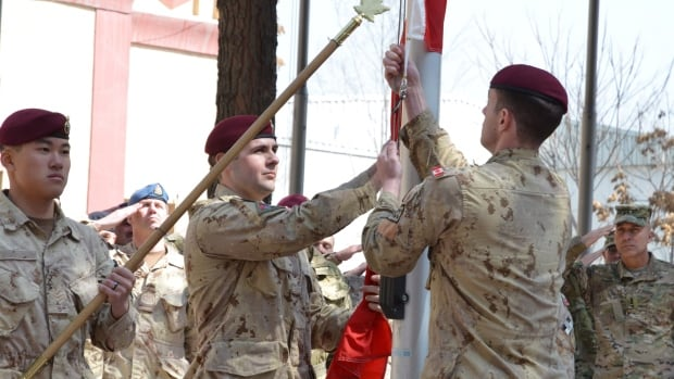 Master Cpl. Daniel Choong (left), Cpl. Harry Smiley (centre) and Cpl . Gavin Early (right) take down the Canadian flag for the last time in Afghanistan on Wednesday March 12, 2014, bringing an end to 12 years of military involvement in a campaign that cost the lives of 158 soldiers.