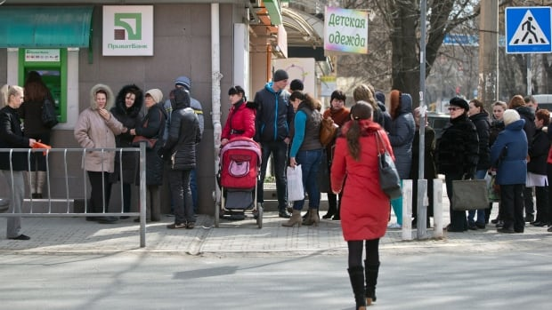 Ukrainians line up to use an ATM after their bank imposed a limit of 1,500 hryvna ($165 Cdn) on daily withdrawals. Ukraine's finance minister says the economy will shrink by 3 per cent in 2014 due to the ongoing crisis.