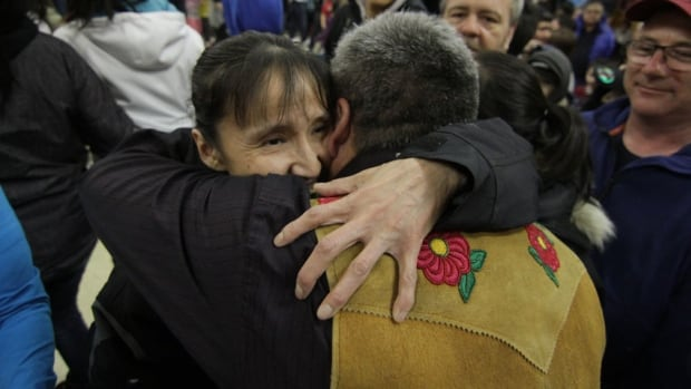 Deline's chief negotiator Danny Gaudet hugs a community member after the results of the self-government vote were announced.
