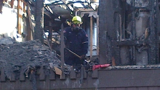 A fire investigator rakes through the debris of one of the units that was damaged by fire on Wednesday.