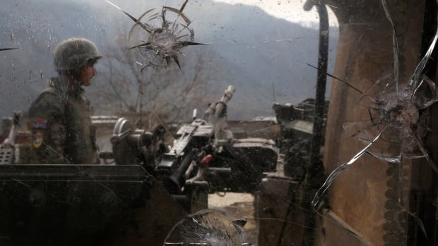 An Afghan National Army  soldier is seen through damaged glass as he keeps watch at the Forward Base in Nari district near the army outpost in Kunar province in February. The Taliban's information arm says Canadians departing Afghanistan have followed other NATO nations' forces in 'retreat and failure.'