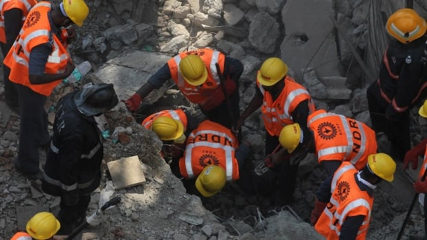Rescue workers search for survivors in the debris of a building that collapsed in Mumbai, India, Friday.
