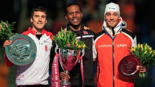 Shani Davis of the U.S. holds the trophy after winning the men's 1000-metre speedskating event of the World Cup final along with Canadian Denny Morrison, left, and third-place Kjeld Nuis, right, of the Netherlands, at Thialf skating arena in Heerenveen, northern Netherlands on Friday.