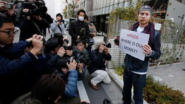 Kolin Burges (R), a self-styled cryptocurrency trader from London, holds a placard to protest against Mt. Gox as photographers take photos of him in front of the building where the digital marketplace operator was formerly housed in Tokyo, on Feb. 26, 2014.