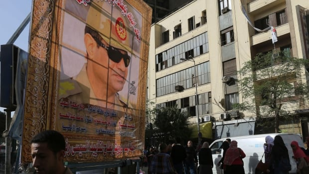 People walk past a huge banner for Egypt's army chief, Field Marshal Abdel Fattah al-Sisi, in downtown Cairo on March 4. Sisi has indicated he will run for president.