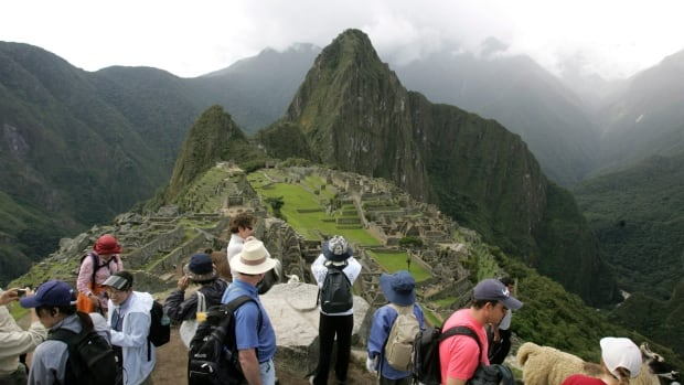 Tourists look at the Inca citadel of Macchu Picchu in Peru. Two Canadians were arrested for taking nude photos of each other at the archaeological monument.