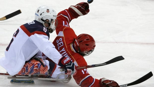 American sledge hockey player Declan Farmer, left, skates into the back of Russian player Vadim Seyukin during the gold medal game at the Sochi Paralympics on Saturday.