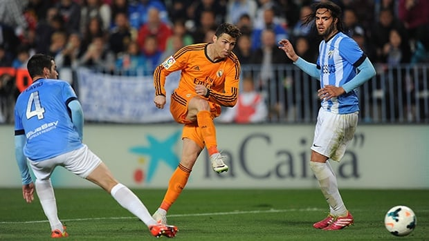 Cristiano Ronaldo of Real Madrid, centre, shoots during the match against Malaga at La Rosaleda Stadium on March 15, 2014 in Malaga, Spain.