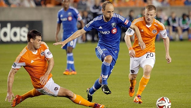 Montreal Impact midfielder Justin Mapp, centre, avoids the tackle from Houston Dynamo players during the first half in Houston.