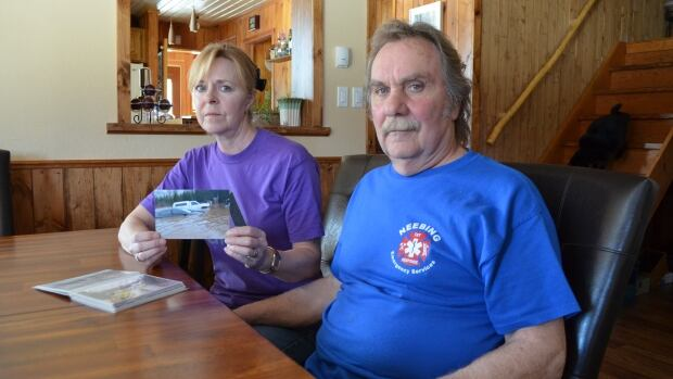 Joanne Cannady holds up a photo of two vehicles submerged in water after a flood at the Neebing home she shares with husband Robert Casavant.
