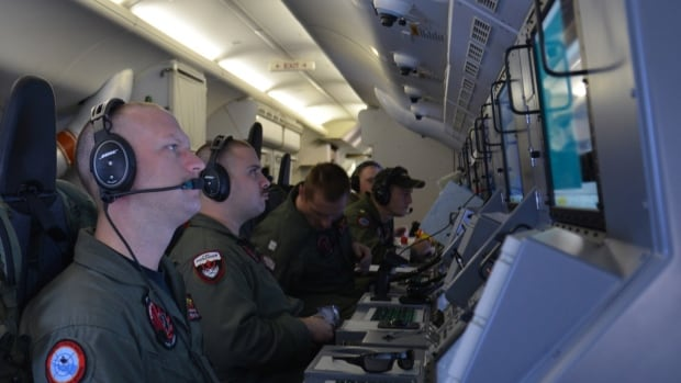 U.S. Navy crew members on board the aircraft P-8A Poseidon assist in search and rescue operations for Malaysia Airlines flight MH370 in the Indian Ocean.