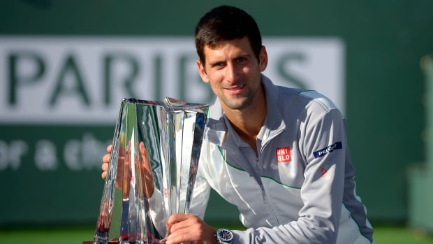 Novak Djokovic poses with the trophy after beating Roger Federer in the final match of the BNP Paribas Open on Sunday, March 16, 2014, in Indian Wells, Calif.