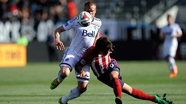 Chivas USA forward Erick Torres and Vancouver Whitecaps defender Jay DeMerit during the first half at StubHub Center.