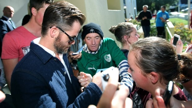 Hollywood actor Chris Pine, left, is surrounded by people outside a courthouse in Ashburton, New Zealand on Monday.