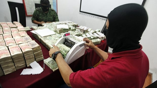 Military officers count money seized during an operation outside Monterrey. Officials say Mexican drug cartels are venturing into new businesses outside narcotics.
