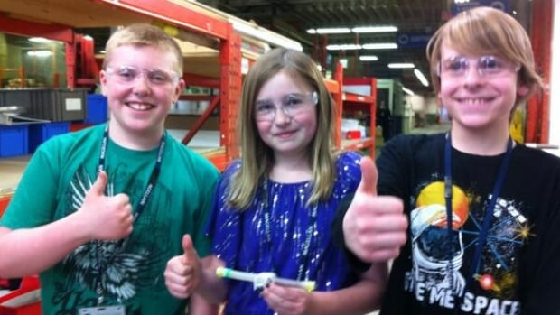 Brant-Argyle School kids Ryan Petricig, Avery Good and Ethan Enns hold up a test tube from their space experiment at Winnipeg's Magellan Aerospace centre this past March.