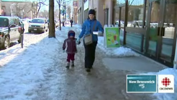 Janique LeBlanc and her daughter Ev hold hands on the slippery sidewalks in Fredericton.